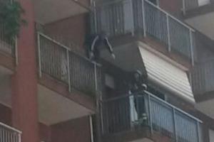 Nella foto l'uomo in piedi sul balcone e il pompiere che cerca di tranquillizzarlo (Spf)